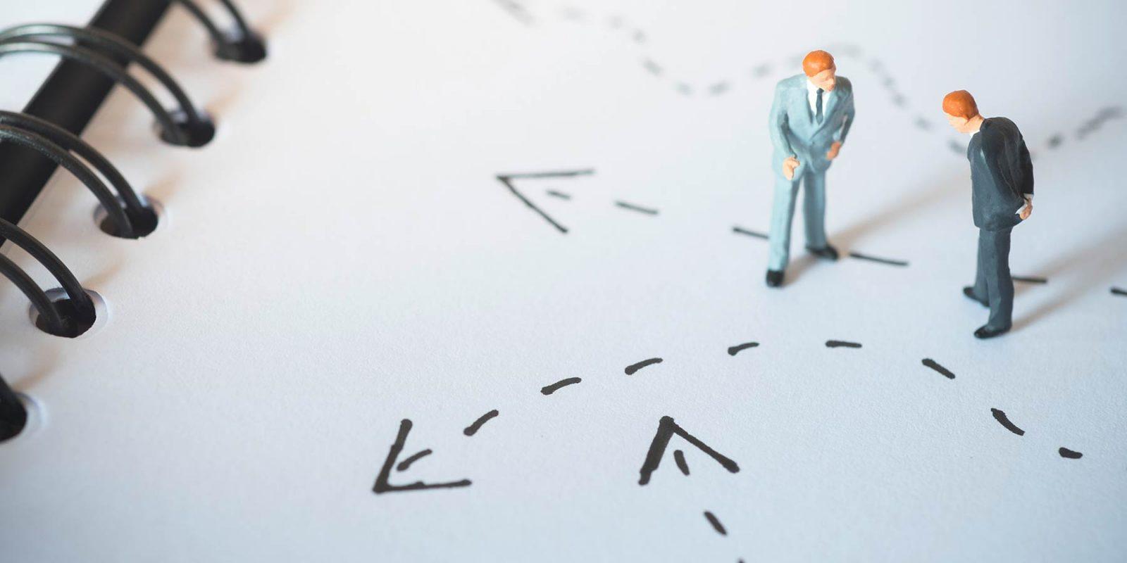 Miniaturfiguren auf einem Notizblock platziert (Konzeptfoto Entscheidungshilfe)